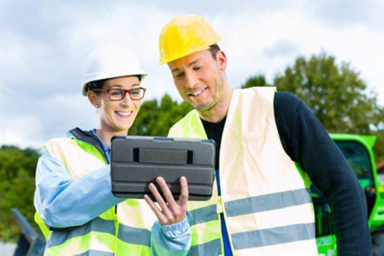 Baustellenarbeiter schauen auf ein Tablet
