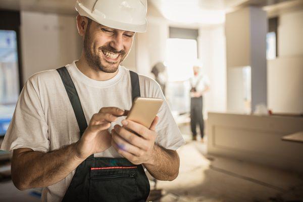 Mit einem Smartphone füllt ein Mann auf der Baustelle ein Bautagebuch aus