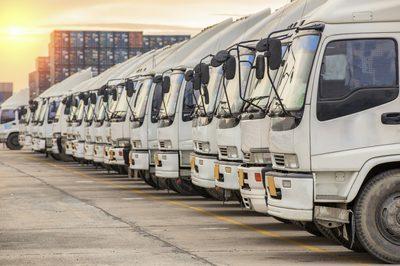 Eine Flotte von LKW auf einem Parkplatz, GPS-Ortung für digitales Fuhrparkmanagement.