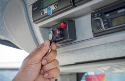 Ein Mann stempelt mit einem RFID Chip in einem Fahrzeug