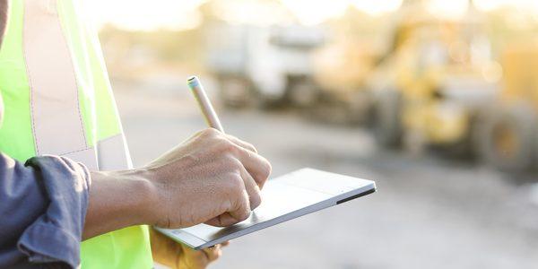 Auf einer Baustelle unterschreibt ein Mann auf einem Tablet ein digitales Bautagebuch